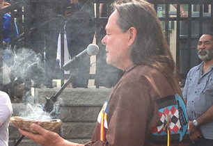 Male adult holding smudging bowl by a microphone