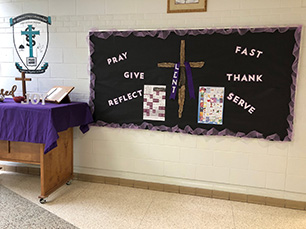 table with purple cloth and Lenten messages on a bulletin board