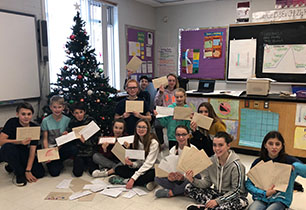 Group of students holding their letters and cards to Canadian Military around a Christmas Tree