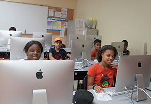 Two female and three male students sitting at Mac book computers