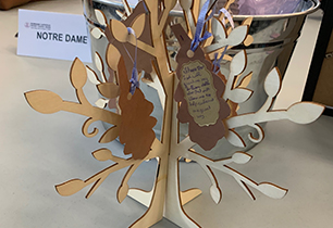 Mini wooden tree with messages on acorn leaves on a table